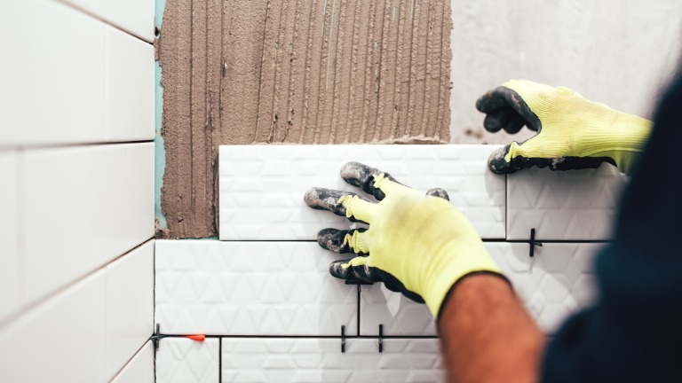 Construction worker installing small ceramic tiles on bathroom walls picture id679511934
