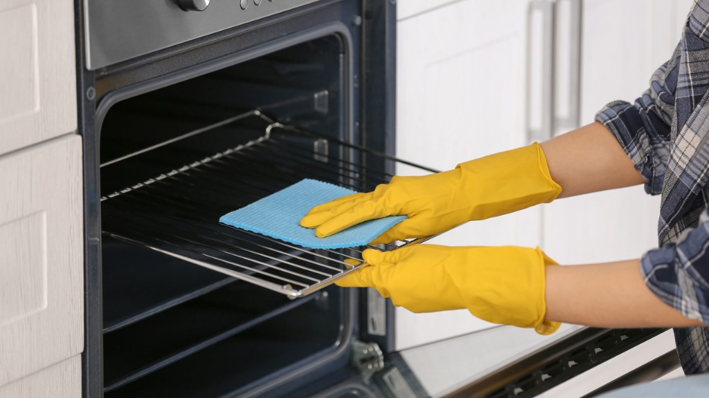 Woman cleaning oven in kitchen closeup picture id942141666