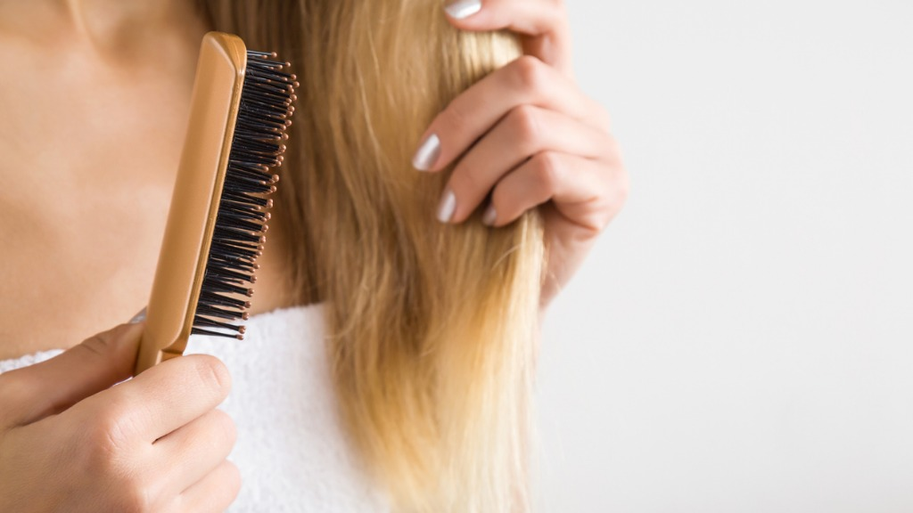 Womans hand brushing blonde hair cares about a healthy and clean hair picture id852239992